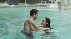 Medium panning shot of couple relaxing in swimming pool / Arenal, La Fortuna, Stock Footage