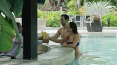 Wide panning shot of couple toasting in swimming pool / Arenal, La Fortuna, Stock Footage