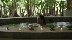 Slow motion zoom in shot of woman soaking in hot tub / Arenal, La Fortuna, Costa Stock Footage