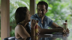 Close up of shot of couple toasting with tropical drinks at bar / Arenal, La Stock Footage
