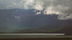 Heavy Luminous Storm Clouds Over Canadian Mountain Lake and Waterfall - stock footage
