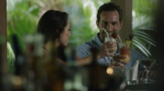 Medium shot of couple toasting with tropical drinks in bar / Arenal, La Fortuna, Stock Footage