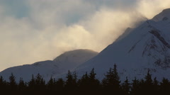 Huge Clouds of Blowing Snow Spindrift Off Mountain Peaks over Forest Stock Footage
