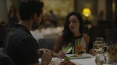Medium tracking shot of man feeding girlfriend in restaurant / Arenal, La Stock Footage