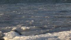 Icy Chunks and Slush Coming Ashore Frigid Waves Sunny 4K Stock Footage