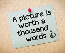 Recycled paper note pinned on cork board with motivational message - stock photo