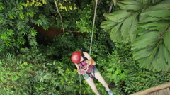 High angle wide tracking shot of woman ziplining to rain forest floor / Quepos, Stock Footage