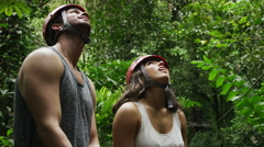 Medium shot of couple admiring zipliners in rain forest / Quepos, Puntarenas, Stock Footage