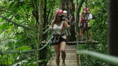 Medium slow motion shot of woman walking on wooden rope bridge / Quepos, Stock Footage