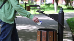 Young man throwing away paper trash, litter bin, dumpster, park, nature, garbage Stock Footage