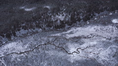 Looking Down Aerial Alaskan Winter River Channels and Snowy Forest Stock Footage