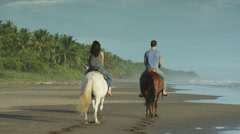 Wide slow motion panning shot of couple riding horseback on beach / Esterillos, Stock Footage