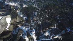 Low Aerial over Waves Splashing on Icy Rocks Stock Footage
