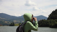 Tourist hiker with binoculars on a windy day on a mountain lake trip Stock Footage