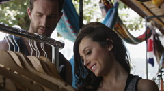 Tilting close up shot of couple shopping in clothing store / Jaco, Puntarenas, Stock Footage