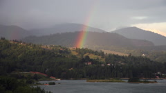 Beautiful rainbow disappearing after big storm, mountain, lake, magic colors Stock Footage