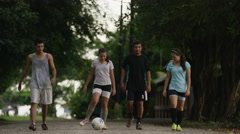 Wide panning shot of soccer team walking on dirt road / Esterillos, Puntarenas, - stock footage