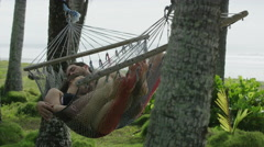 Medium panning slow motion shot of couple napping in hammock / Esterillos, - stock footage