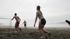 Wide slow motion panning shot of people playing soccer on beach / Esterillos, Stock Footage