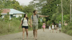 Medium panning shot of couple walking on dirt road / Esterillos, Puntarenas, Stock Footage