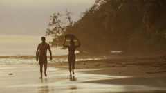 Wide panning shot of couple carrying surfboards on beach / Esterillos, Stock Footage