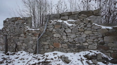 Stone Ruins Foundation Wall in Winter Pan Left - stock footage