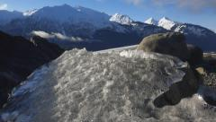 Weatherworn Ice Chunk on Rocky Shoreline in Sunny Alaska Slide Right Stock Footage