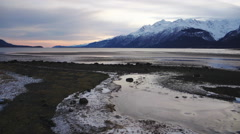 Winter Afternoon Flight over Icy Rocky Beach Low Tide Chilkat Inlet - stock footage