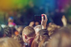 Fans Photographing Music Band Live Performing on Stage - stock photo