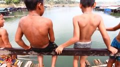 Young boy jumping into lake on Wooden bridge Stock Footage