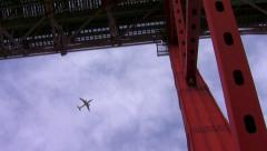 Airplane passing flying over a red bridge Stock Footage