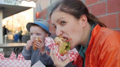 Family eating fast food for dinner outside diner Stock Footage