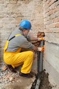 Plumber at construction site installing sewerage tube - stock photo
