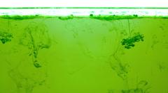 Ink swirling in green liquid under oil layer loop 4K Stock Footage