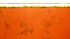 Ink swirling in orange liquid under oil layer loop 4K Stock Footage