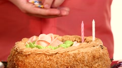 Baby handles decorate a cake with candles, inserting one by one. close up Stock Footage