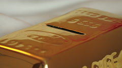 Throw money into a gold bar 01 Stock Footage