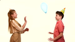 Smiling children holding balloons and embracing each other on a white background Stock Footage