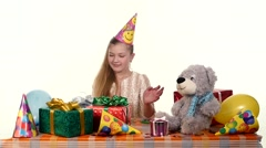 Stock Video Footage of birthday girl looks with admiration at his gifts. around it are soft toys and