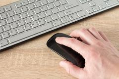 Hand using wireless computer mouse Stock Photos