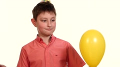 boy eats yellow balloon with a needle and frightening explosion slow motion - stock footage