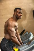 Muscular black male bodybuilder exercising on treadmill in gym - stock photo