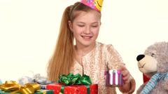 Birthday girl sitting at the table sees boxes with gifts and wants to determine - stock footage