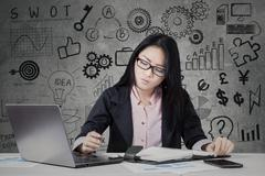 Busy entrepreneur working with laptop and planner - stock photo