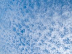 Lots of cloud dots on a partly cloudy blue sky - stock photo