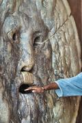 "Hand entering the famous ""mouth of truth"" in the church of Santa Maria in cos - stock photo"