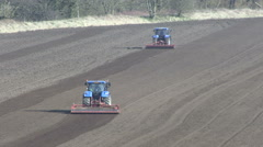 Two tractors tilling a field. - stock footage