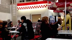 Young people enjoying meal at food court with front motion blur fries. Stock Footage