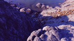 DOLLY MOTION: Precipice sandy rocks near the lake shore June. Color-style film - stock footage