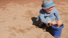 Cute boy filling bucket with sand on beach Stock Footage